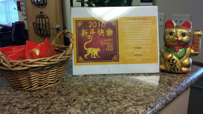 A basket of red envelopes and a Chinese calendar placed on a counter
