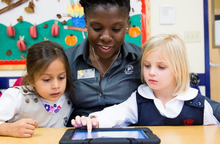 image of teacher and two students using an ipad