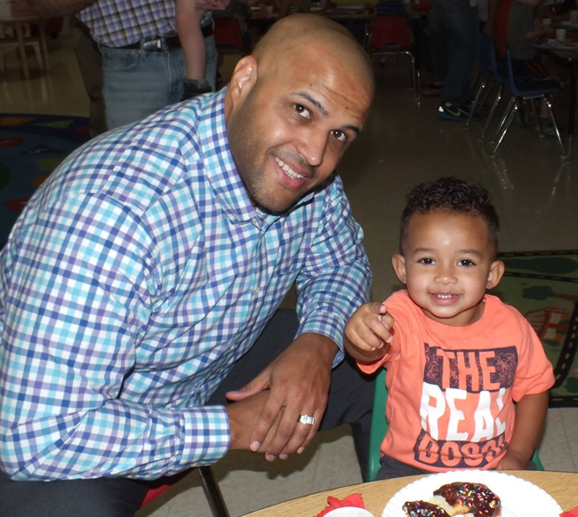 Father and his little toddler son enjoying a plate of donuts