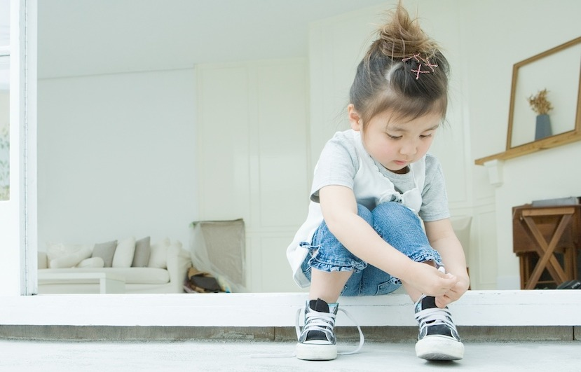 image of little girl tying shoes