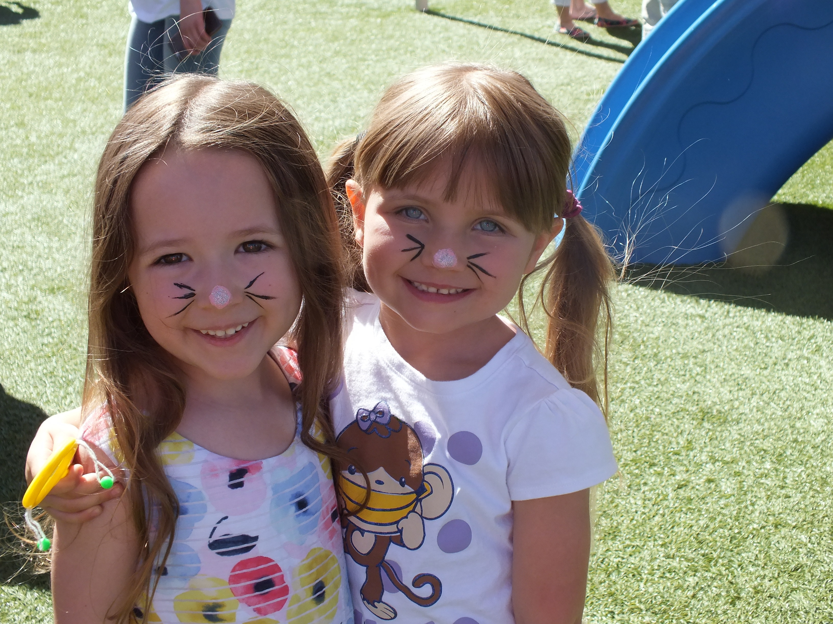 Two little girls with whiskers painted on their faces celebrating spring fling
