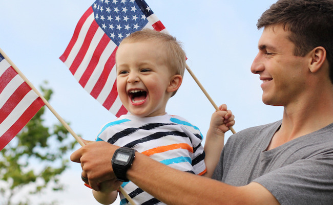 image of father holding son and American flags