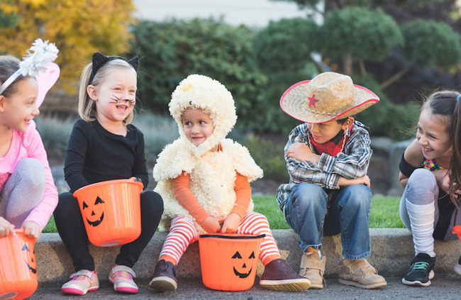children dressed up in Halloween costumes sitting on a curb