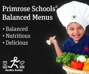 A Primrose student joyfully holds a basket full of vegetables