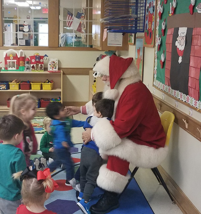 santa hugging small children at school