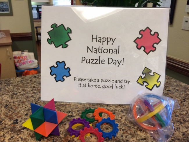 """Sign wishing everyone """"Happy national puzzle day"""" with three different puzzles placed next to it"""