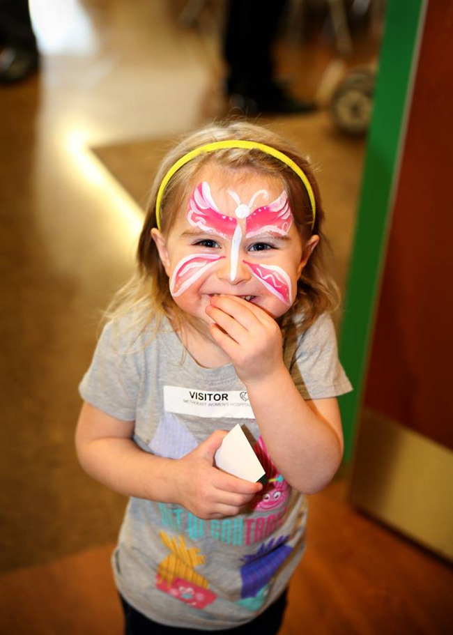 Little girl with a butterfly painted on her face smiles