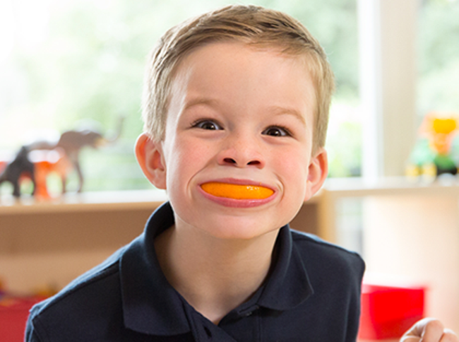 Young Primrose student smiles excitedly with a slice of orange in his mouth