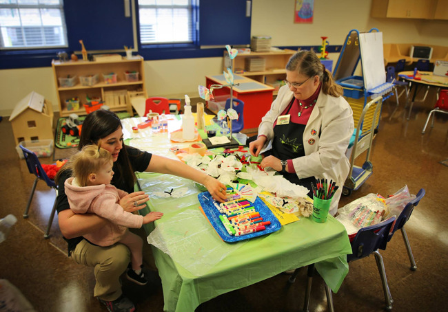 Primrose teacher sits with a toddler on her lap and shows her a science experiment, while another teacher cuts paper