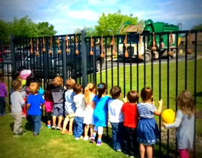Pre-school students line up by the school gate to see the garbage truck