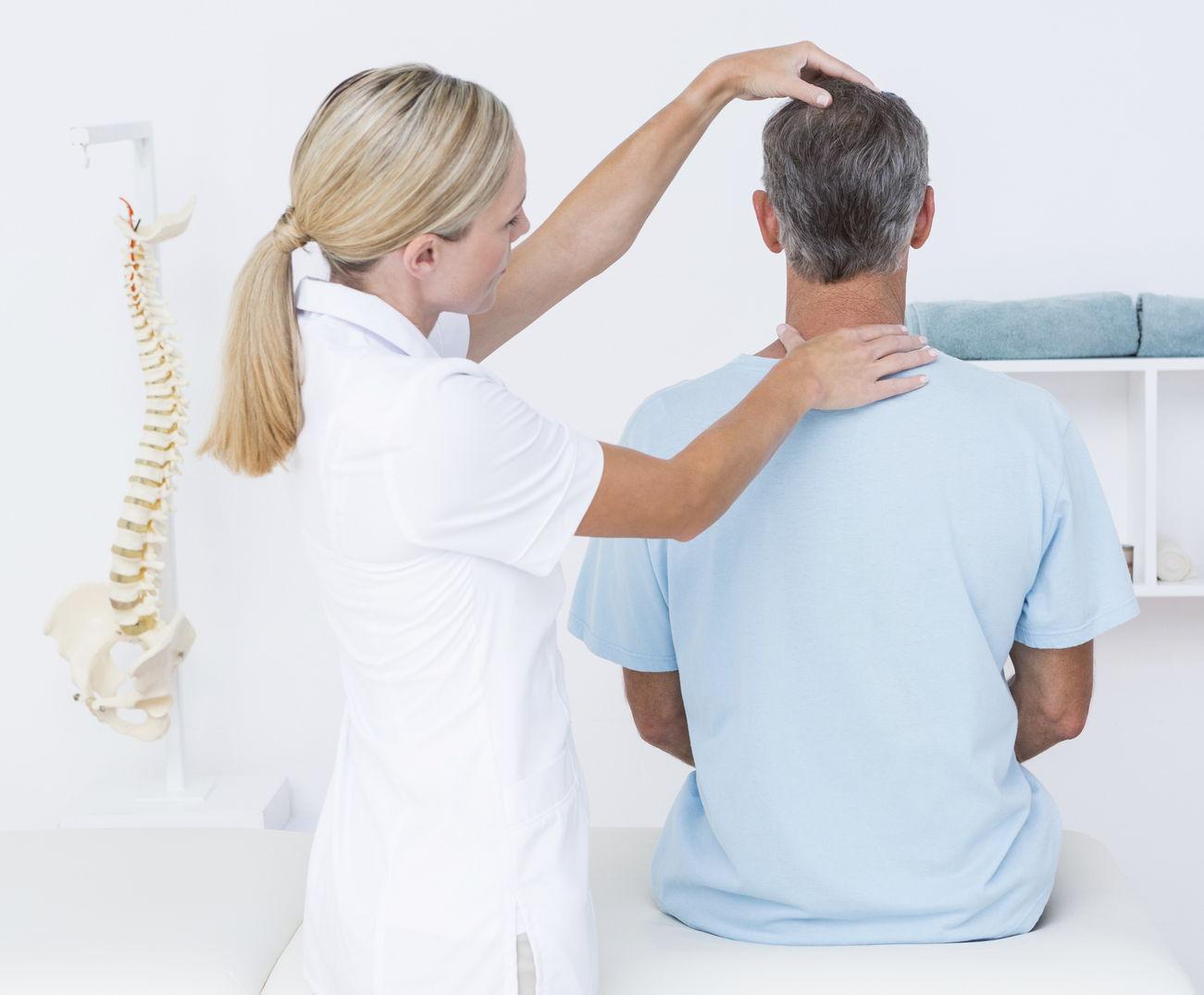Una dottoressa visita un paziente nel corso di una visita ortopedica di controllo