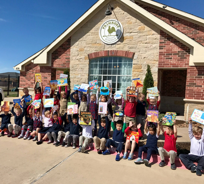 Primrose students hold up storybooks and pose for a group picture outside the school entrance