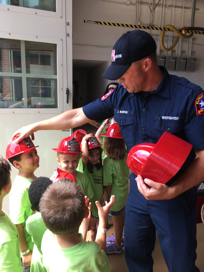 A fire fighter from Station #1 in Flower Mound TX passes out fire hats to Summer Adventure Club students