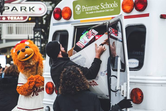 Man loads box full of toys into the Primrose school of East Allen school bus as the Frisco rough riders mascot looks on