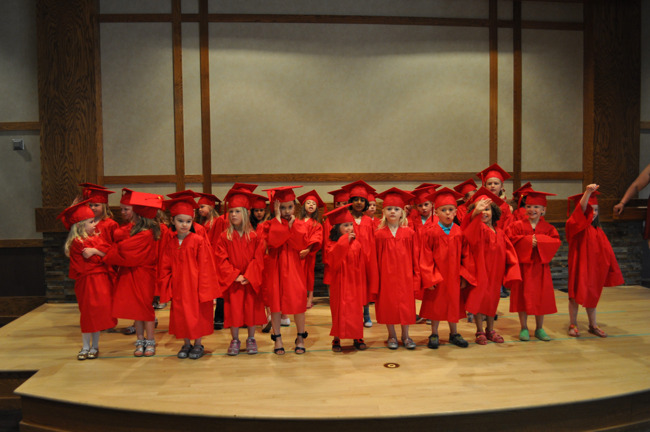 Young Primrose students at their graduation ceremony in caps and gowns