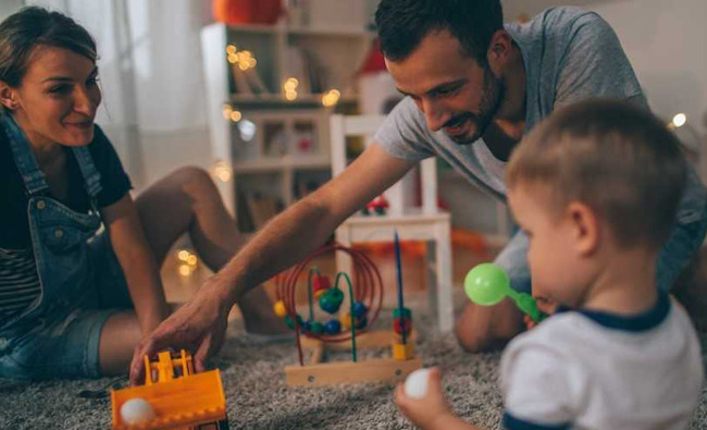 image of parents playing with toys with their child