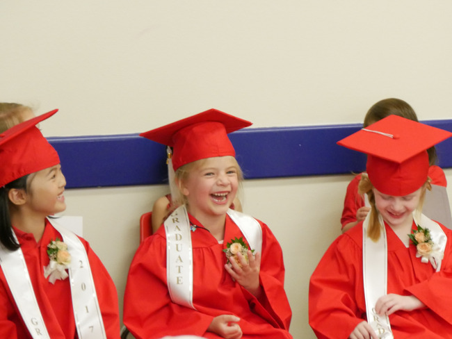 Primrose graduates wearing caps and gowns laugh as they wait for their turn at the graduation ceremony