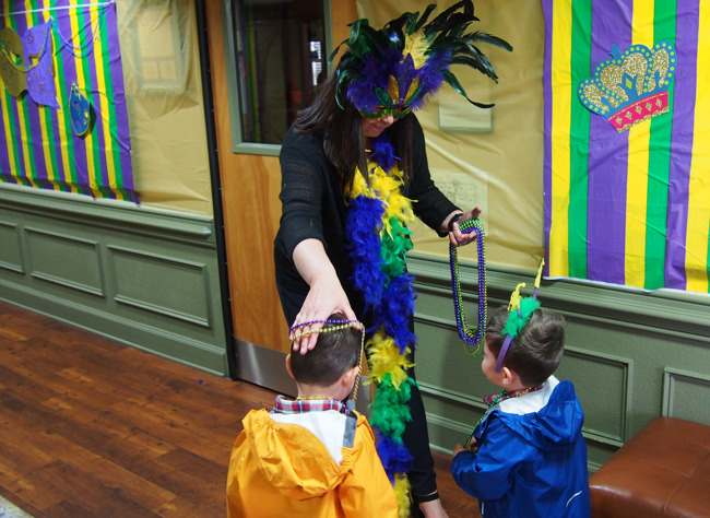 kids receive beads from Director at Mardi Gras celebration