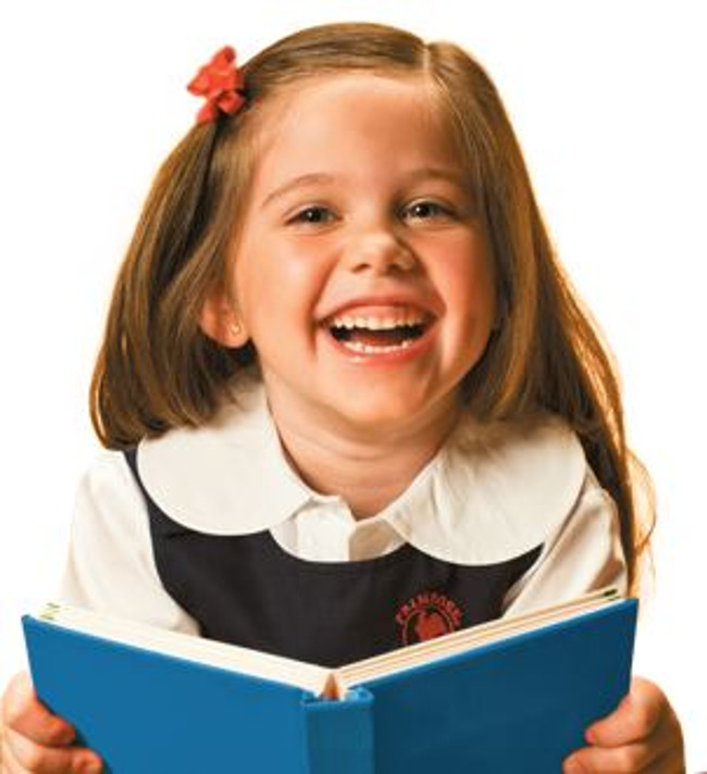 Young Primrose student holds a book and giggles heartily
