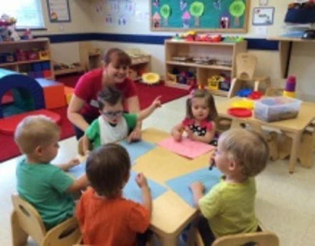 Primrose toddler students sit with drawing sheets and crayons in class as their teacher interacts with them