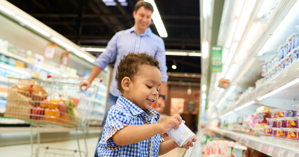 Little toddler picks up yogurt in the supermarket as his father watches him