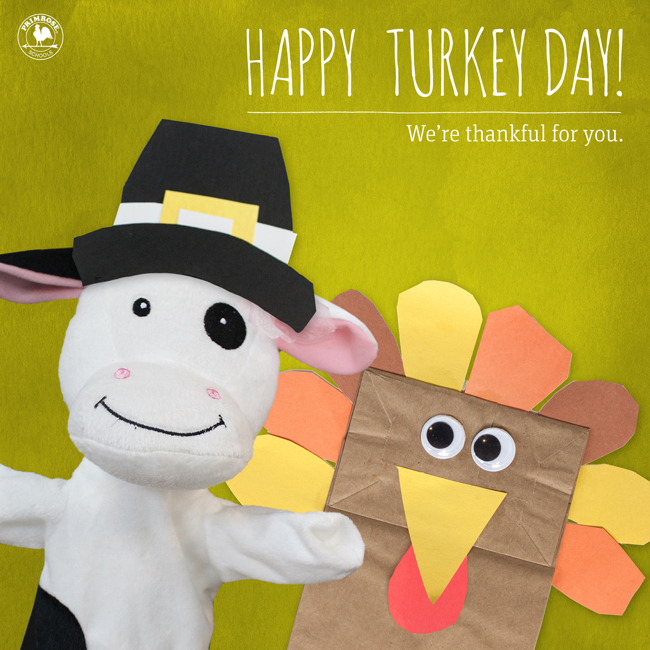 "A cow puppet wears a pilgrim hat next to a paper bag turkey, with the text ""Happy Turkey Day!"""