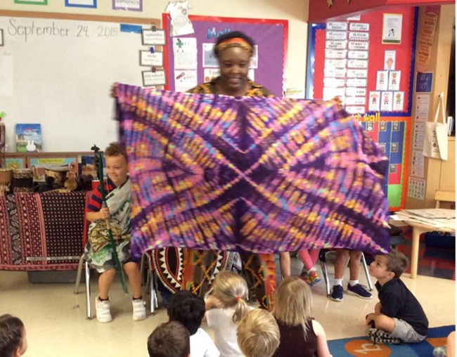 Mrs. Elizabeth holds up a hand dyed scarf as she teaches the students about African Culture
