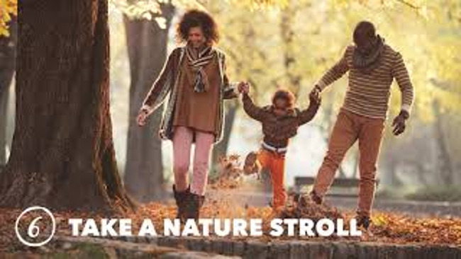 Mother and father swing their young son as he holds their hands and walks in the park on a beautiful fall day