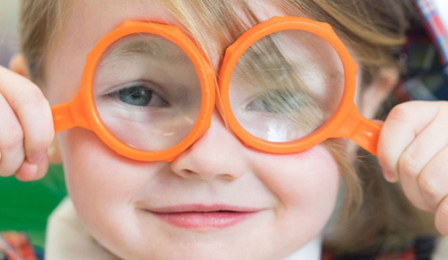 image of little girl holding up magnifying glasses over her eyes