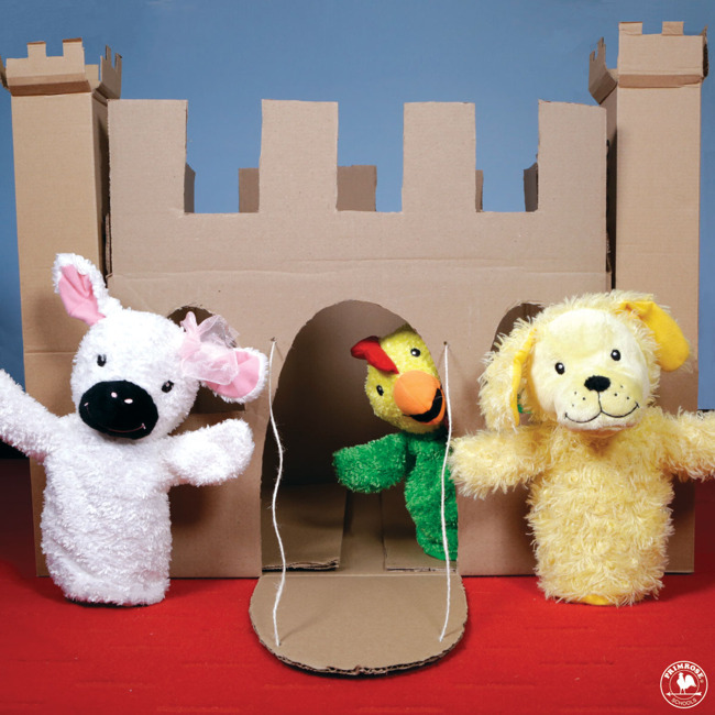 Primrose puppet Percy the chicken peeks out from a cardboard castle while Libby the lamb and Erwin the dog stand outside