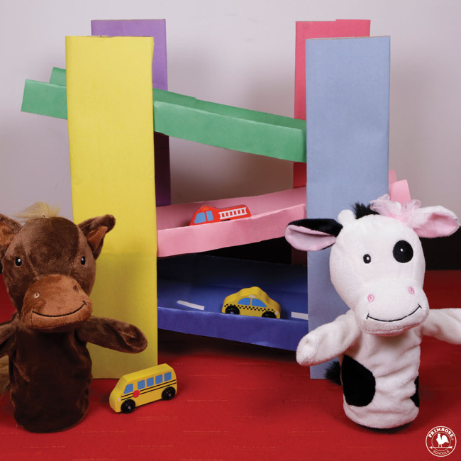 Primrose puppets Peanut the Pony and Molly the cow stand next to a homemade racetrack
