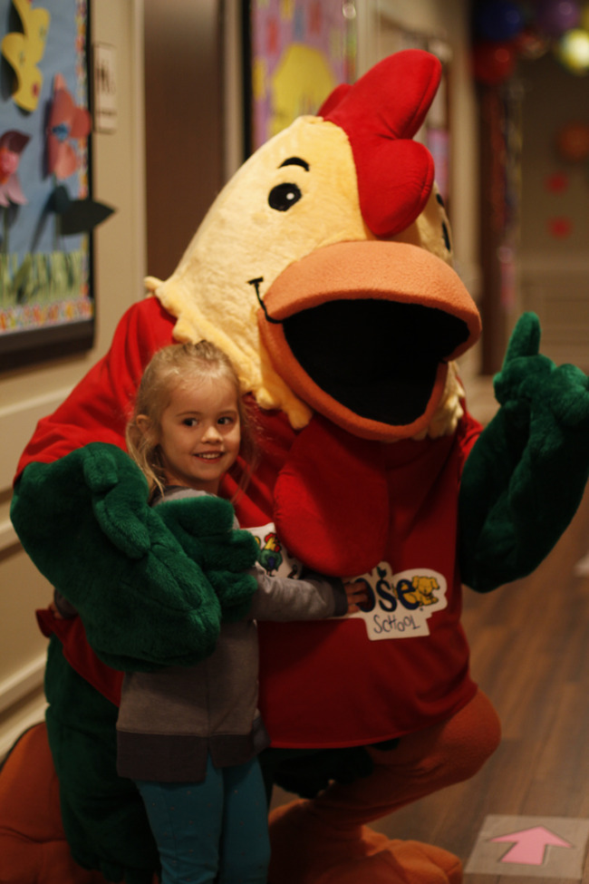Young Primrose student looks happy as she is hugged by Percy the chicken mascot