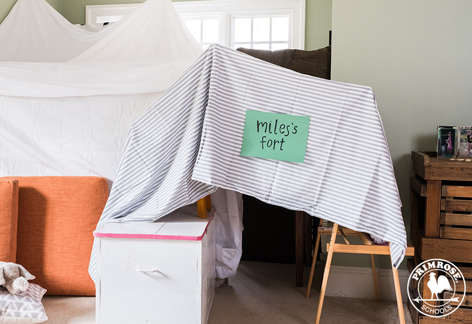 "Indoor fort made with bed sheets and chairs labelled ""Miles's Fort"""