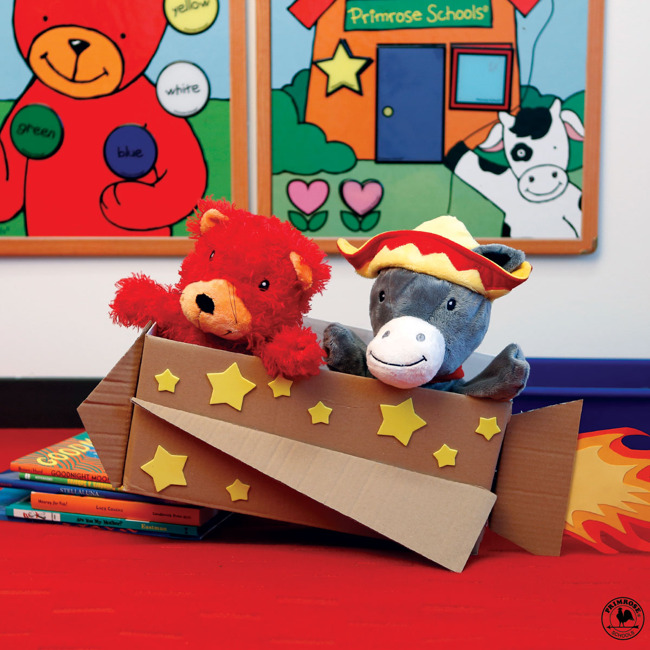 Primrose puppets Arturo the burro and Benjamin the bear sit in a cardboard rocket ship