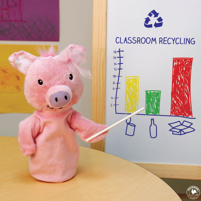 Primrose puppet Megy the pig points to a graph about classroom recycling