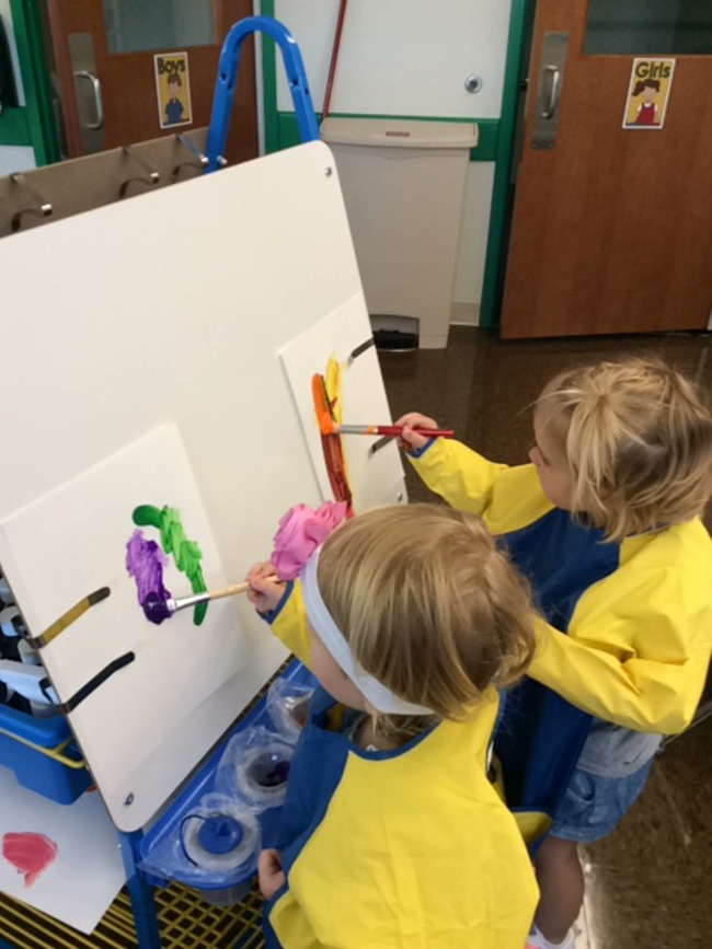 Two young Primrose toddlers paint on canvases mounted on stands
