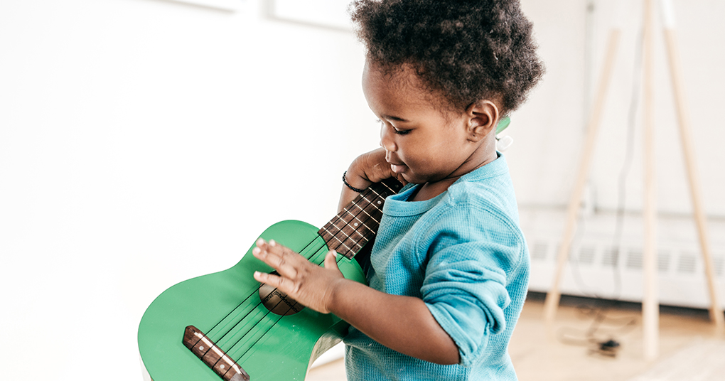 Little toddler tries to strum a ukelele