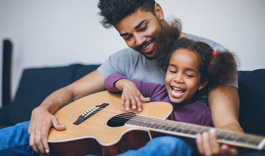 dad and daughter playing a guitar