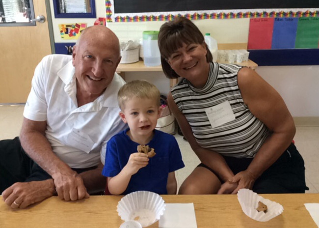 A Primrose student enjoying a cookie with his grandparents