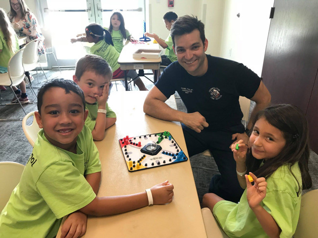 Image of three children playing a board game with a firefighter around a table.