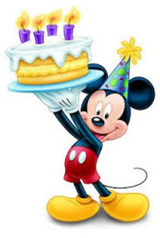 Mickey mouse wears a birthday cap and stands with a cake
