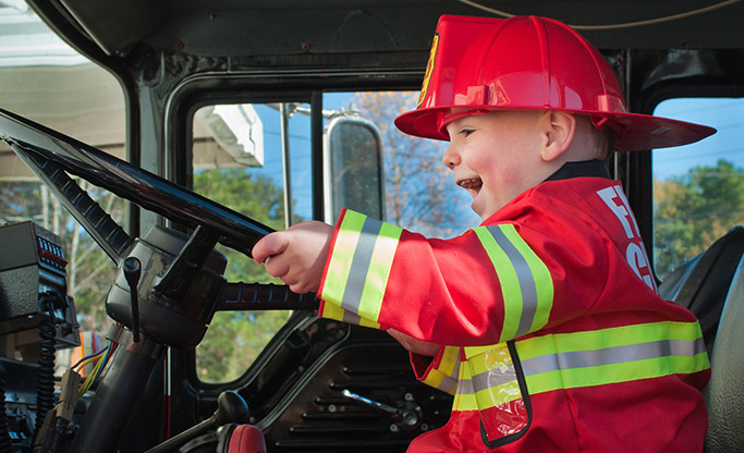 image of young boy driving a firetruck