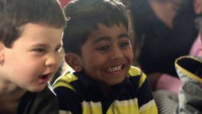 A close up of two young boys; one looks excited and the other looks confused