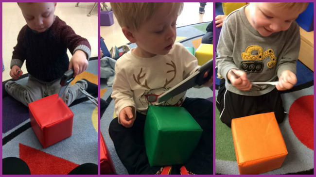 Primrose Early Preschool students sit with a large foam cube for their tools and machines activity