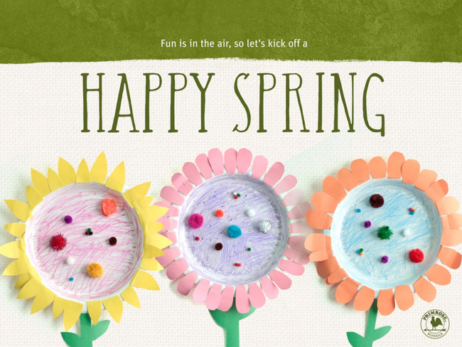 "Handcrafted paper plate flowers are on a tan background with the words ""Happy Spring"" in green above them"
