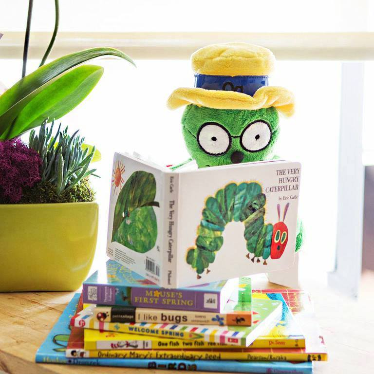 "Og the Bookworm puppet sits on a stack of children's books, reading ""The Very Hungry Caterpillar"""