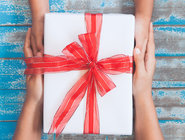 image of children's hands holding a gift together