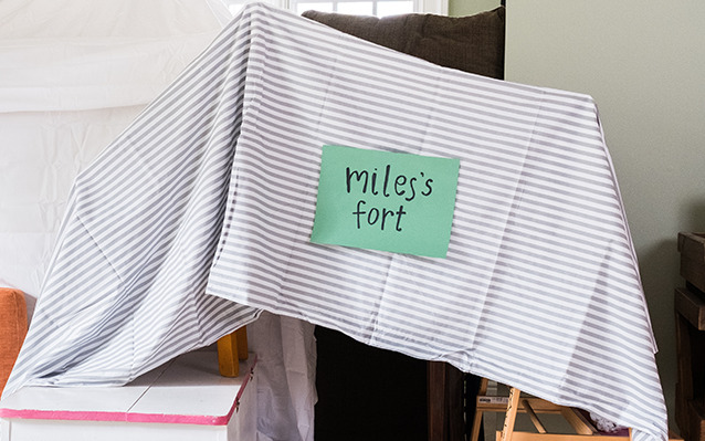 "Indoor fort made out of bed sheets and chairs labelled ""Miles's fort"""