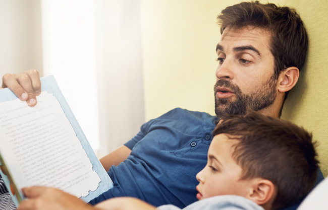 image of father reading a bedtime story to son