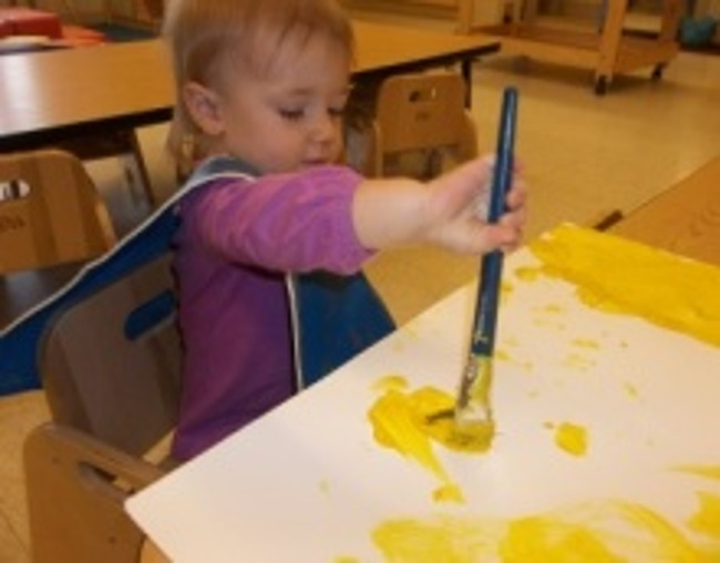 Little infant girl paints with a brush on a large sheet of paper in a Primrose classroom